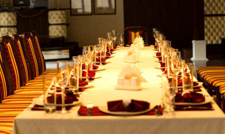 Elegant formal table set with red linen accents, stylish glassware, silverware and centerpieces for a party , reception or festive celebration, view down the length photo