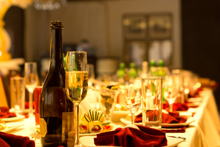 Champagne in a bottle and elegant tall flute on a formal dinner table set with luxury linen and glassware with red accents for a celebration and party
