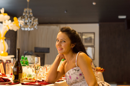 Beautiful woman sitting alone at a formal dinner table set with elegant place settings, glassware and champagne leaning her chin on her hand giving the camera a warm friendly smile photo