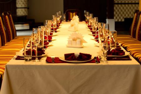 リネン、エレガントなガラス、銀製品、特別なイベントのためのセンター ピースで赤いアクセントの場所設定で長い間正式なディナー テーブルの長