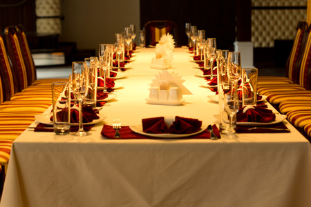 formal dinner party: View down the length of a long formal dinner table with red accented place settings with linen, elegant glassware, silverware and centerpieces for a special event