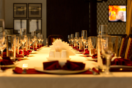 venue: Dining table set with elegant place settings with red linen accents for a formal party or celebration in a restaurant or club, low angle view down the length of the table