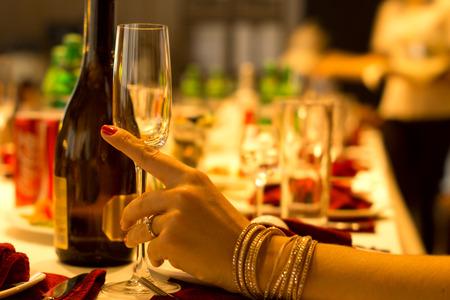 Mujer con estilo vistiendo oro potable joyas champ�n de una flauta con estilo en una cena formal apoyando la mano sobre la mesa con dof bajo y un ambiente brillante caliente