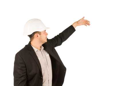inscrutable: Young Caucasian Male Engineer in Black Coat Showing Something. Captured in Half Body Portrait. Stock Photo