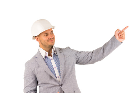 unemotional: Close up Smiling Engineer on White Helmet and Gray Coat Pointing Side. Isolated on White Background.
