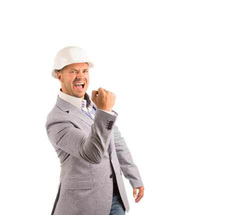 unemotional: Very Happy Middle Age Male Engineer on Gray Coat and White Helmet Looking at Camera. Emphasizing He Got Something Good. Isolated on White Background. Stock Photo