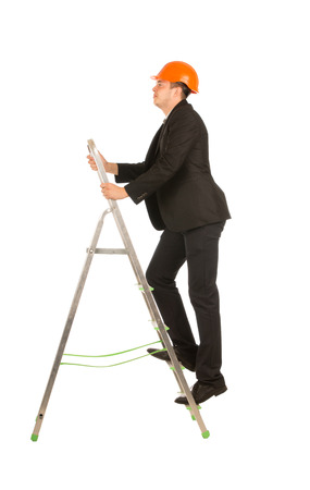 Middle Age Male Engineer on lack Coat and Orange Head Protector Posing at Small Portable Steel Ladder. Isolated on Full White Background. photo