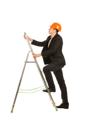 Young Male Engineer on Black Suit and Orange Helmet Posing at Portable Ladder. Emphasizing Going Up. Isolated on Full White Background. photo