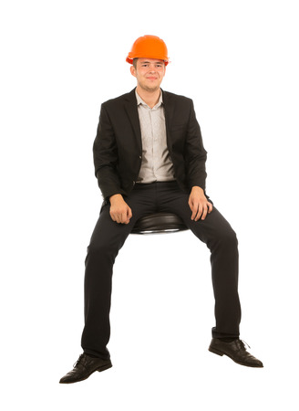 Smiling Sitting Young Male Engineer in Black Suit and Orange Head Protector Looking at Camera. Isolated on White Background. Stock Photo