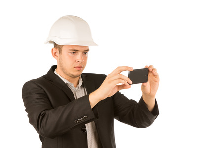 Close up Young Male Engineer in White Helmet and Black Coat Taking Picture Using Mobile Phone. Isolated on White Background. Фото со стока