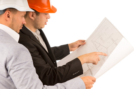 structural engineers: Two young architects or structural engineers standing discussing a building plan or blueprint pointing to certain details of the drawing, side view on white
