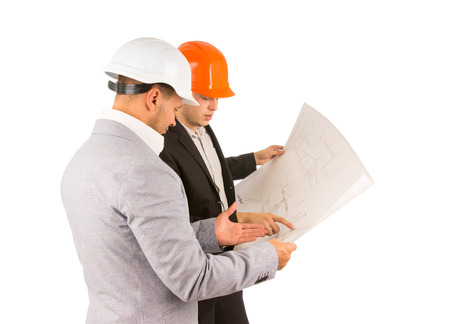 structural engineers: Two young structural engineers or architects wearing hardhats standing discussing a building plan or blueprint pointing to the drawing, side view on white