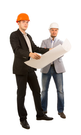 architectural firm: Two partners in an architectural firm standing studying a blue print of a building that one of them is holding, full length on white in suits and hardhats