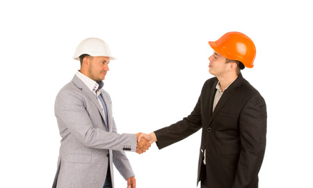Young Client in Black Suit and Orange Helmet Shaking Hand with Engineer in White Helmet. Isolated on White Background. photo