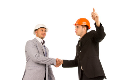 Two Young Angry Male Engineers in Gray and Black Coats Shaking Hands on White Background. photo