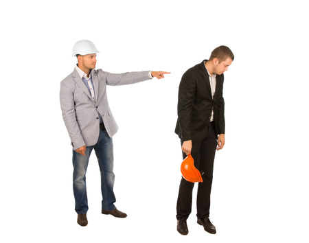 reprimanding: Head Engineer in White Helmet and Gray Coat Pointing Subordinate While Reprimanding. Isolated on White Background. Stock Photo