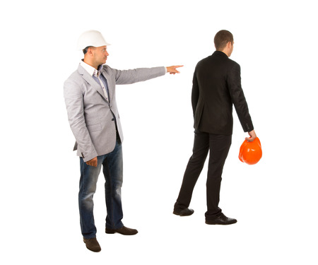 abject: Head Engineer in White Helmet Pointing His Subordinate Engineer Wearing Black Attire with Orange Helmet. Captured on White Background. Stock Photo