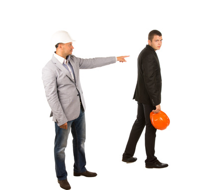 Middle Age Engineer in Gray Coat Pointing his Co-Engineer Wearing Black Attire Holding Orange Helmet. Captured on White Background.