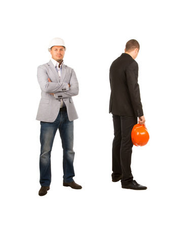 abject: Two Middle Age Engineers with Orange and White Helmets Facing Different Directions. One is Looking at Camera While the Other is Facing at the Back. Isolated on White Background. Stock Photo