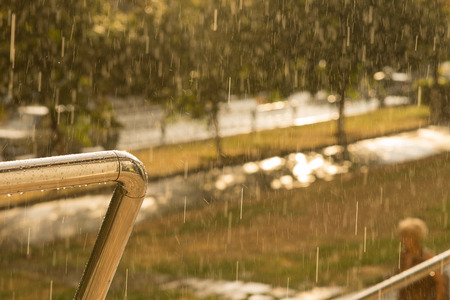 hand rail: View from a balcony of a park through pouring rain with focus to the hand rail and water droplets Stock Photo