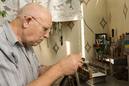 meticulous: Close up Serious Old White Man Working For Electronic Device on Table with Paraphernalia.
