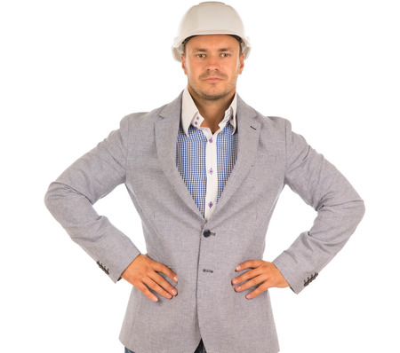 unemotional: Confident determined architect or engineer wearing a hardhat and jacket standing staring straight ahead with his hands on his hips, isolated on white Stock Photo