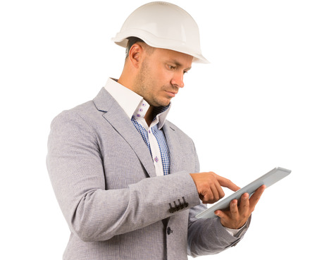 Side view of an architect or engineer using a tablet navigating the touch screen with his finger, isolated on white Stock Photo
