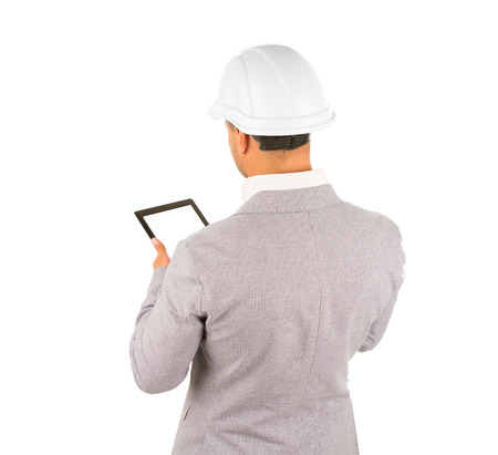 View from behind of an architect in a hardhat standing using a tablet computer, isolated on white Stock Photo
