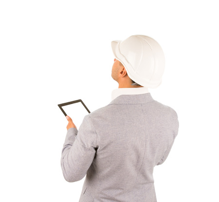 taskmaster: Over the shoulder rear view of an architect or building inspector in a hardhat using a tablet with the blank screen partially visible, isolated on white Stock Photo