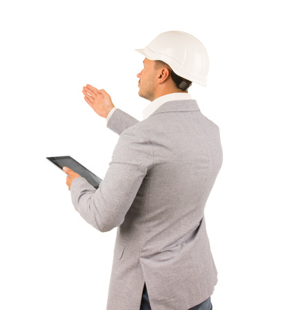 superintendent: Architect or engineer showing something with his hand pointing to his right side as he stands side on to the camera with a tablet in his hand, isolated on white