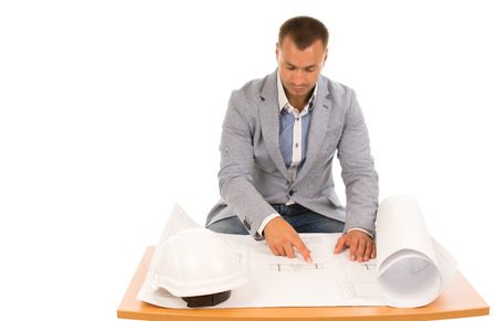 Construction foreman or engineer working on a blueprint sitting at a table reading specification with his hardhat alongside, isolated on white photo