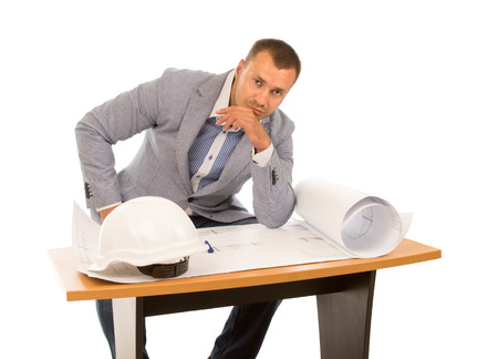 Architect sitting working on a plan at a table pausing to stare at the camera with a serious expression, isolated on white photo