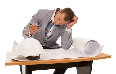 seeking an answer: Architect solving a problem on a building plan sitting at a small wooden table with his head on his hand and pen in the other, isolated on white