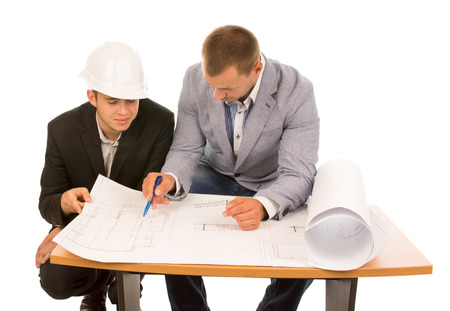 feasibility: Team of architects working on a plan seated side by side at a table discussing the open blueprint, isolated on white