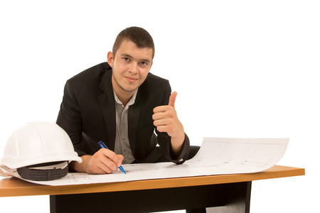Smiling architect giving a thumbs up gesture of success as he sits at a table working on a building plan, isolated on white photo