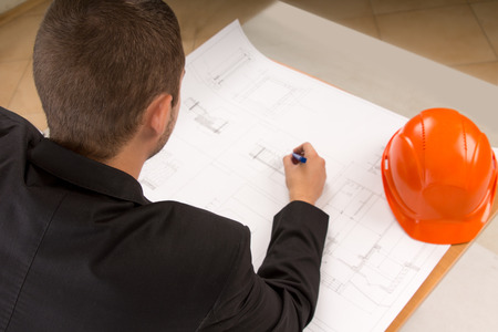 Over the shoulder view of a young architect with a pencil in his hand modifying a building plan as he sits at a table with his hardhat alongside photo