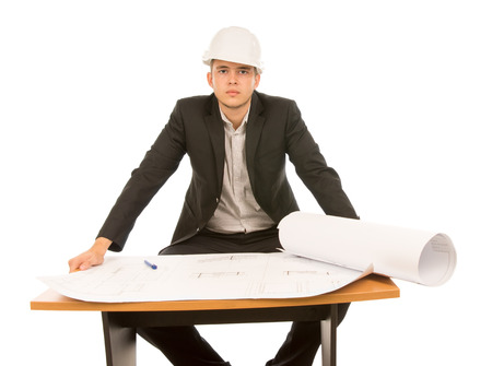 Confident young architect with a blueprint open in front of him sitting at a table looking directly at the camera, isolated on white photo