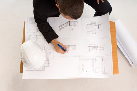 View from above of an architect drafting or modifying a building plan with his hardhat alongside photo