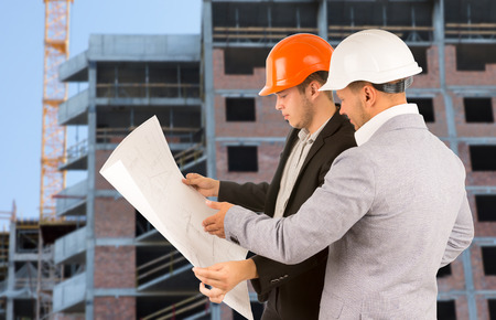 Two architects or engineers standing discussing a building blueprint as they stand on a building site in front of a half completed high-rise building