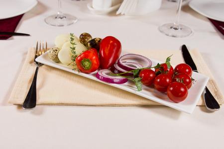 accompagnement: Assiette de l�gumes frais en accompagnement d'un repas avec des tomates cerises rouges, poivrons doux, rondelles d'oignon, les champignons et les herbes sur un plateau rectangulaire Banque d'images