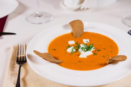 melba: Delicioso plato de calabaza o butternut sopa se sirve con tostadas melba y aderezado con hierbas frescas