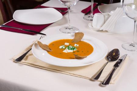 melba: Placa de la calabaza sabrosa o sopa de nogal con queso, tostadas melba y hierbas servidos a la mesa en un lugar formal establecimiento de plata y copas de vino Foto de archivo