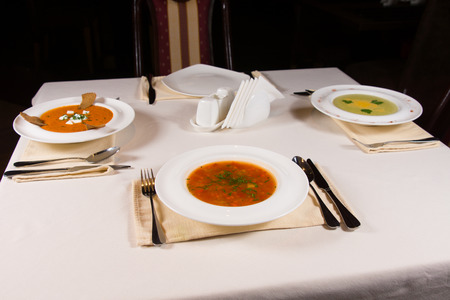 plating: Table set with three different bowls of gourmet vegetable soup with artistic plating in white bowls for an appetizer to a formal dinner