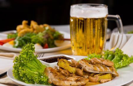 mouth watering: Close up Meat and Vegetable Combination Dish with Mug of Cold Beer. Served on White Dining Table.