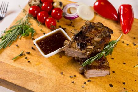 고기의: Tasty Meaty Main Dish with Hot Dip Sauce on Wooden Chopping Board with Spices on Sides.