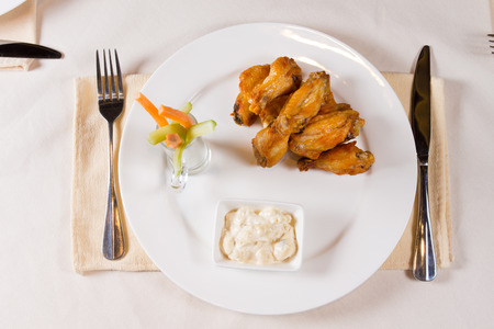 Overhead of Chicken Wings on Plate at Place Setting in Restaurant photo