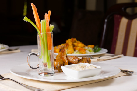 Chicken Wings with Carrots and Celery and Dip on Restaurant Table photo