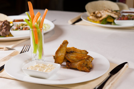 Chicken Wings with Vegetables and Dip at Place Setting on Restaurant Table photo