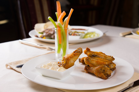 Chicken Wings Appetizer with Vegetables and Dip on Restaurant Table photo