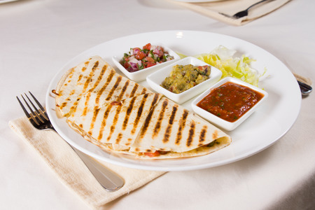 Grilled Quesadilla on Plate with Variety of Salsas and Toppings at Place Setting Stock Photo